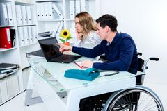 Disabled business man greeting his female colleague. Disabled businessman in wheelchair greeting his female colleague stock photo