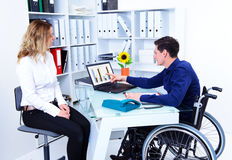 Disabled business man and his female colleague. Disabled businessman in wheelchair and his female colleague stock image