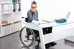 Disabled business man in wheelchair is sorrowful. In the office stock image