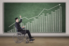 Disabled businessman with financial chart on chalkboard Stock Photos