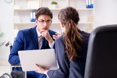 The disabled businessman having discussion with female colleague. Disabled businessman having discussion with female colleague Royalty Free Stock Image