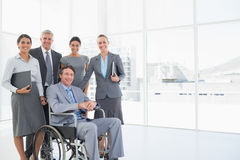 Disabled businessman with his colleagues smiling at camera. In the office stock photography