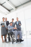 Disabled businessman with his colleagues smiling at camera. In the office royalty free stock image