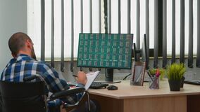 Disabled businessman taking notes in business office