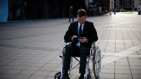 Disabled businessman sitting in wheelchair outdoor and work with tablet PC. stock video
