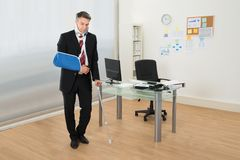 Disabled businessman standing with crutches royalty free stock photo