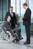 Disabled businessman talking with his co-workers Stock Photography
