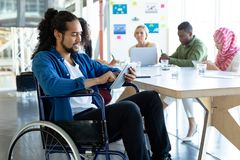 Disabled businessman using digital tablet in conference room during meeting. Front view of Mixed-race disabled businessman using digital tablet in conference royalty free stock photography