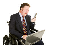 Disabled Businessman - Yelling. Disabled businessman in wheelchair yelling into his cellphone.  Isolated on white Royalty Free Stock Photography