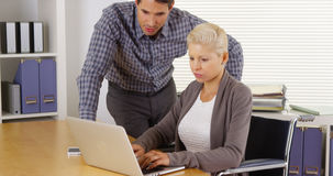 Disabled businesswoman and colleague working together Stock Image