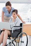 Disabled businesswoman looking at laptop with her colleague Royalty Free Stock Photo