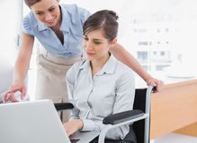 Disabled businesswoman showing co worker her laptop Stock Photography