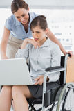 Disabled businesswoman showing colleague her laptop Royalty Free Stock Image