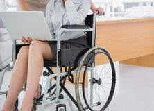 Disabled businesswoman showing laptop to colleague. In an office stock photos