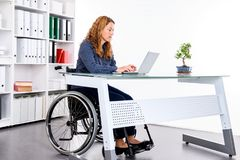 Disabled businesswoman in wheelchair. Working in the office stock photography
