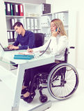 Disabled businesswoman in wheelchair and her colleague Royalty Free Stock Images