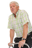 Disabled casual mature man. On white background, using walking frame or Zimmer stock photography