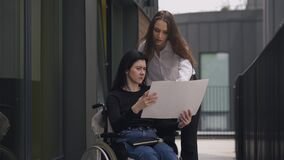 Disabled Caucasian CEO in wheelchair discussing business project with assistant outdoors. Serious successful women