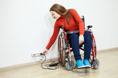 Disabled Caucasian woman in wheelchair stretching to power socket in wall for turn on laptop Stock Image
