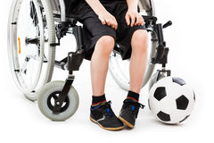 Disabled child boy sitting on wheelchair holding soccer ball. Invalid or disabled child boy sitting on wheelchair hand holding soccer sport ball white isolated royalty free stock photography