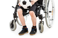 Disabled child boy sitting on wheelchair holding soccer ball Stock Images