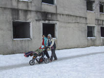 Disabled child in a poor family. Bucharest, Romania, January 13, 2008: Parents carry their disabled child on a go-cart, in front of an abandoned building located Royalty Free Stock Photo