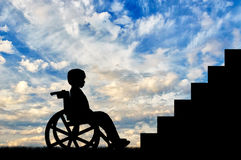 Disabled child sitting in wheelchair front of stairs. Day. Disabled children concept royalty free stock photo