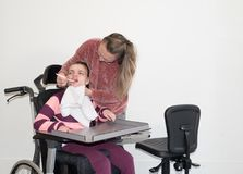 A disabled child in a wheelchair together with a voluntary care worker. A disabled child in a wheelchair being cared for by a voluntary care worker who is Royalty Free Stock Image
