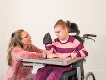 A disabled child in a wheelchair together with a voluntary care worker. A disabled child in a wheelchair being cared for by a voluntary care worker who is Stock Images