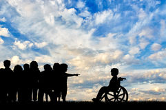 Disabled child in wheelchair and children banish him Royalty Free Stock Photo