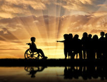 Disabled child in wheelchair and children chased him near sea reflection. Sunset. Concept disabled child Stock Photo