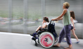 Disabled child in a wheelchair on a city street royalty free stock photos
