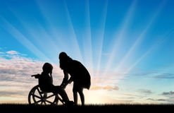 Disabled child in wheelchair crying and his mother day. Concept of disability royalty free stock image