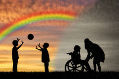 Disabled child in wheelchair crying and his mother near children play with ball Royalty Free Stock Photography