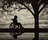Disabled child in a wheelchair crying near tree on beach royalty free stock photos