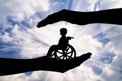 Disabled child in a wheelchair in the hands of man Stock Image