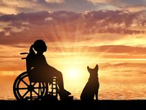 A disabled child in a wheelchair and her dog on a background of sea sunset. Silhouette of a happy disabled child girl sitting in a wheelchair with her dog royalty free stock photography