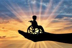Disabled child in a wheelchair in a man's hand. Concept of care and help stock photo