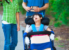 Disabled child in wheelchair outdoors with caregivers or family. Cerebral palsy Royalty Free Stock Photos