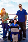 Disabled child in wheelchair outdoors by lake with family. Disabled biracial child in wheelchair outdoors by lake with family. he has cerebral palsy Stock Photos