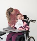 A disabled child in a wheelchair together with a voluntary care worker. A disabled child in a wheelchair being cared for by a voluntary care worker who is Stock Photo
