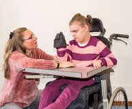 A disabled child in a wheelchair together with a voluntary care worker. A disabled child in a wheelchair being cared for by a voluntary care worker who is Royalty Free Stock Photos