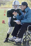 Disabled coach and junior football player. Handicapped coach coaching peewee League football player Royalty Free Stock Image