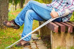 Disabled with crutches in park on bench stock photos