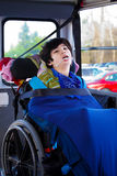 Disabled eight year old boy in wheelchair buckled on school bus Stock Images