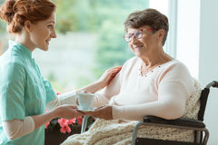 Disabled elder with blanket. Disabled elder women sitting in the wheelchair with blanket and nurse giving her a cup of tea Stock Photos