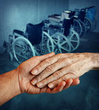 Disabled elderly. Disabled and Handicapped elderly medical health care concept with a young person holding and giving a helping hand to an old elderly Royalty Free Stock Photography