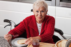 Disabled elderly in kitchen Stock Images