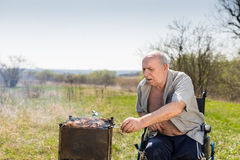 Disabled Elderly Man Grilling at the Park Alone Royalty Free Stock Image