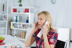 Disabled entrepreneur woman talking to clients on phone Stock Image